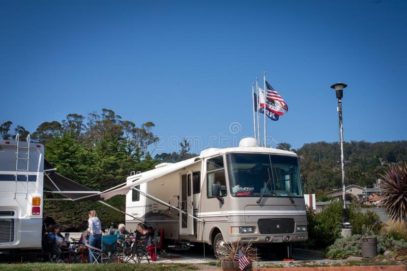 Amerikaanse manier om te kamperen: een familie geniet van vergadering buiten zij monstervrachtwagen stock foto's