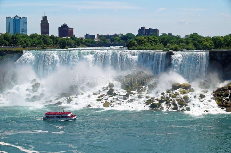 Amerikaanse Niagara valt watervalmening met een toeristisch schipmeisje van de Mist vooraan De dalingenhoogte is 57 m en royalty-vrije stock foto