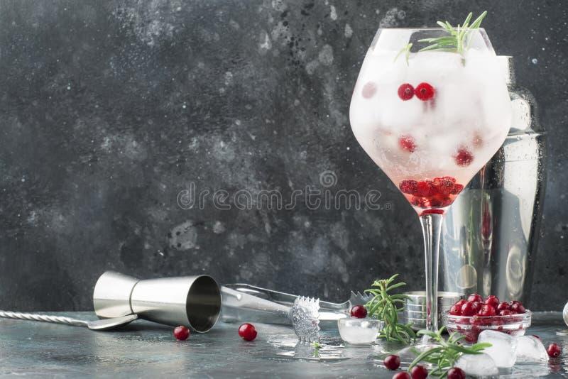 Amerikaanse veenbescocktail met ijs, verse rozemarijn en rode bessen in groot wijnglas, barhulpmiddelen, grijze bar tegenachtergr royalty-vrije stock afbeelding