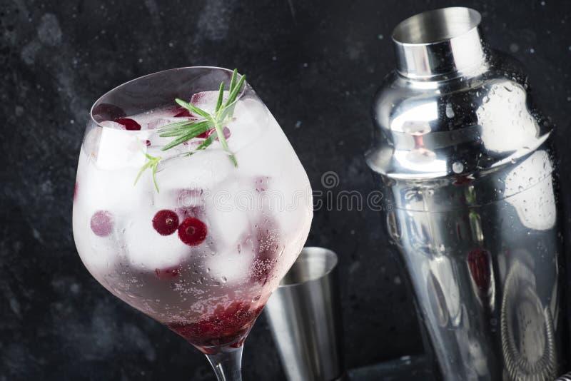 Amerikaanse veenbescocktail met ijs, verse rozemarijn en rode bessen in groot wijnglas, barhulpmiddelen, grijze bar tegenachtergr stock afbeelding