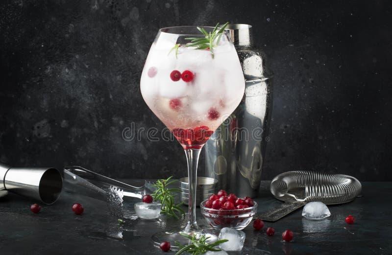 Amerikaanse veenbescocktail met ijs, verse rozemarijn en rode bessen in groot wijnglas, barhulpmiddelen, grijze bar tegenachtergr royalty-vrije stock foto