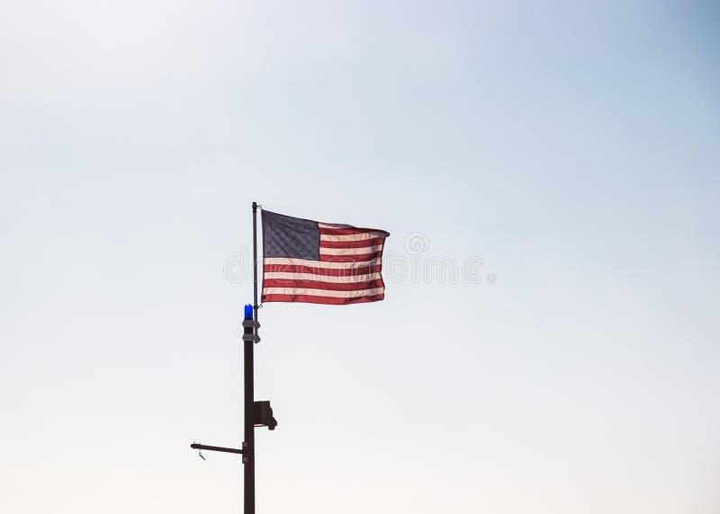Amerikaanse vlag die in de wind tegen een duidelijke, wazige blauwe hemel vliegen royalty-vrije stock fotografie