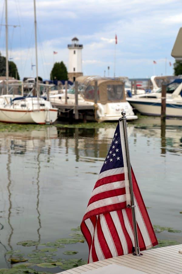 Amerikaanse Vlag in Haven met Boten en Vuurtoren royalty-vrije stock afbeelding