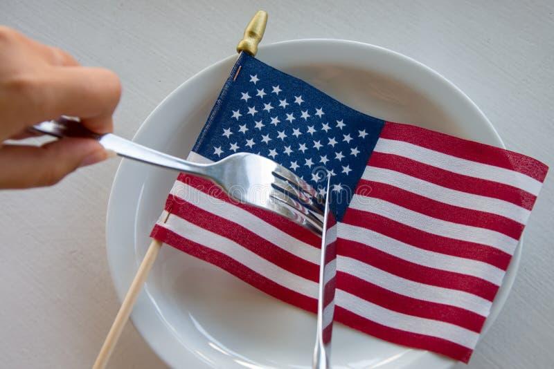 Amerikaanse vlag op een plaat die met een mes en een vork, het conflict in de maatschappij wordt gesneden royalty-vrije stock afbeelding