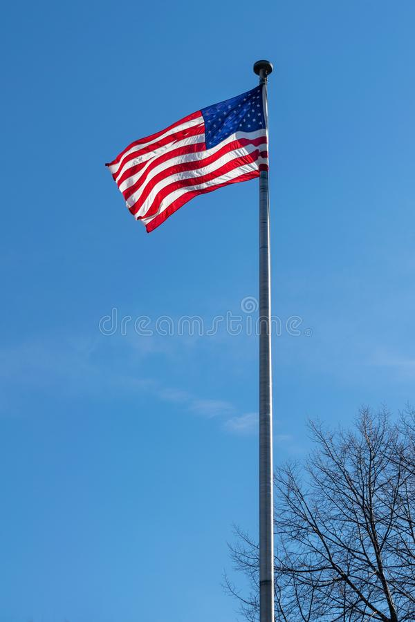 Amerikaanse vlag, Sterren & Strepen, die in de wind, tegen een mooie blauwe hemel op een zonnige de zomerdag golven royalty-vrije stock afbeelding