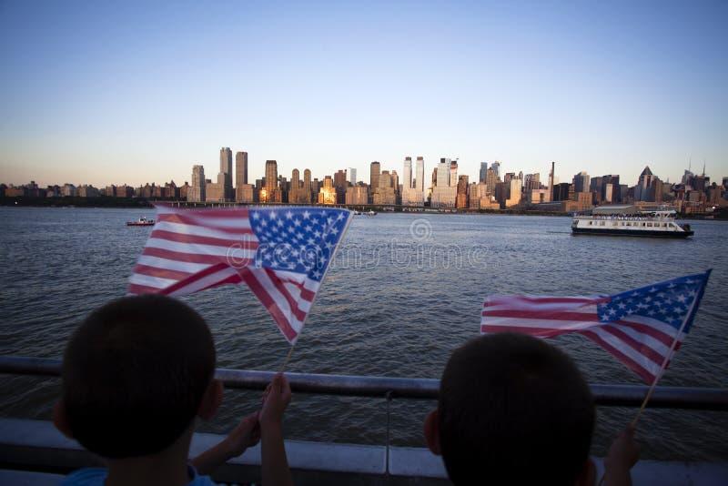 Amerikaanse vlag tijdens Onafhankelijkheidsdag op Hudson River met een mening bij de Stad van Manhattan - van New York - Verenigd stock foto