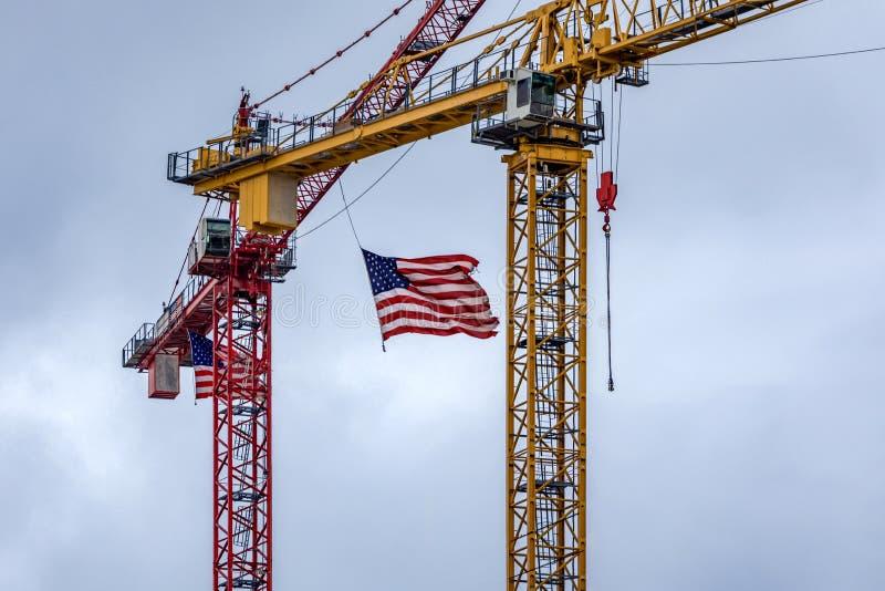 Amerikaanse Vlaggen die op bouwkranen vliegen stock afbeelding