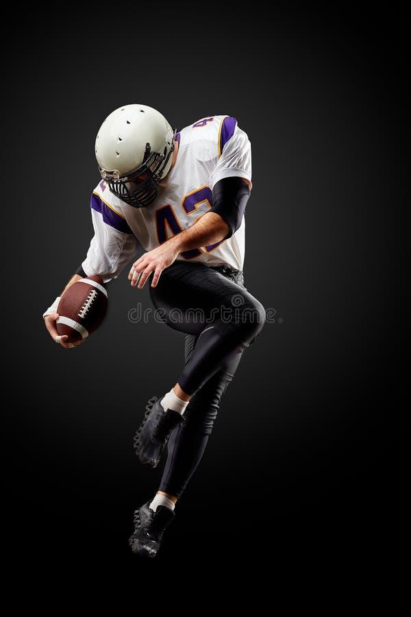 Amerikaanse voetbalster in een sprong met een bal op een zwarte achtergrond stock afbeeldingen