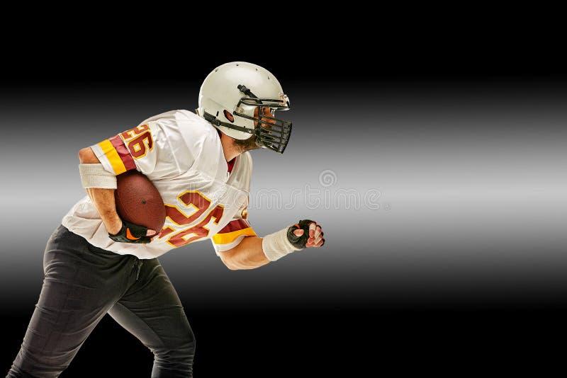 Amerikaanse voetbalster in motie met de bal op een zwarte achtergrond met een lichte lijn, exemplaarruimte Het concept royalty-vrije stock foto's