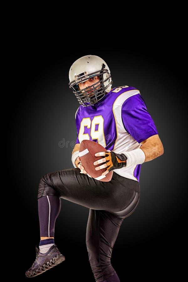 Amerikaanse voetbalster in motie met de bal op een zwarte achtergrond met een lichte lijn, exemplaarruimte Het concept royalty-vrije stock afbeelding