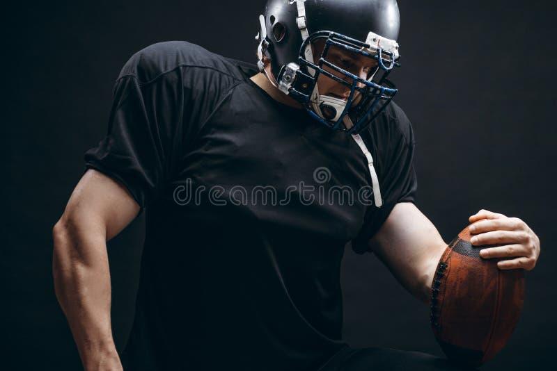 Amerikaanse voetbalster in zwarte sportwear met een bal op zwarte achtergrond stock afbeelding