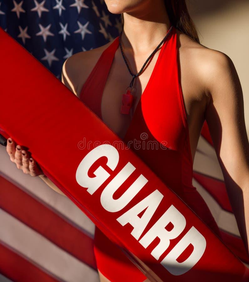 Amerikaanse vrouwenbadmeester met reddingsbuis en fluitjemateriaal tegen de vlag van de V.S. stock fotografie