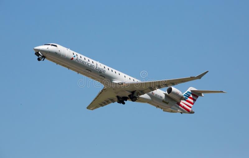 Amerikan Eagle Passenger Jet Flying i en molnfri himmel arkivfoto