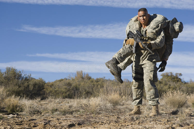 AMERIKANISCHE Armee-Soldat Carrying Wounded Friend stockbilder