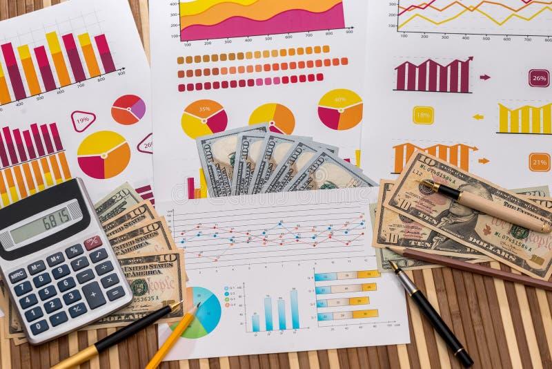 Amerikanische Dollar auf Geschäftsdiagrammen mit Stift und Taschenrechner stockfotografie