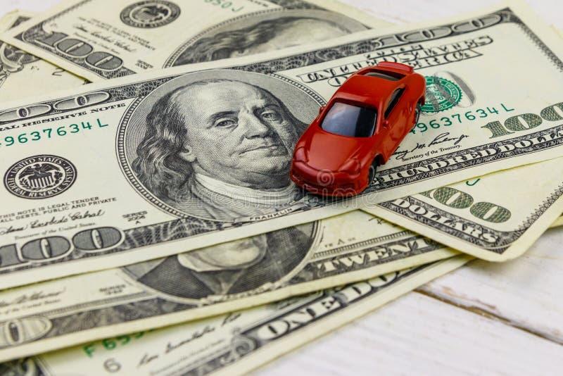 Amerikanische Dollar und Miniaturautomodell auf weißem hölzernem Hintergrund lizenzfreie stockfotografie