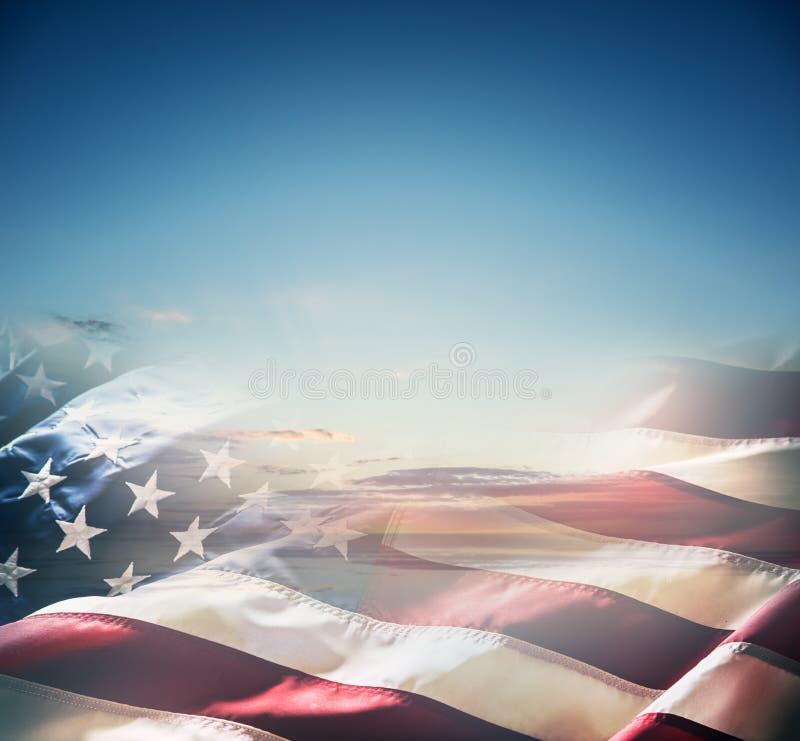 Amerikanische Flagge über einem schönen Sonnenuntergang oder einem Sonnenaufgang lizenzfreie abbildung