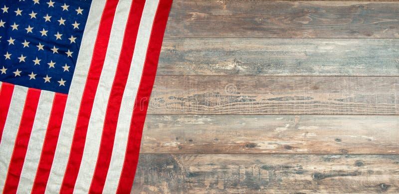 Amerikanische Flagge, die auf einem gealterten, verwitterten rustikalen hölzernen Hintergrund liegt stockbilder
