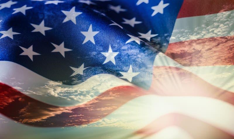 Amerikanische Flagge, die in den Wind bei Sonnenuntergang oder Sonnenaufgang wellenartig bewegt stockfotos