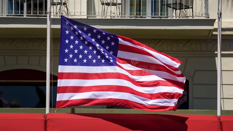 Amerikanische Flagge flattert auf Pfosten vor Gebäude, Patriotismus, Demokratie stockfoto