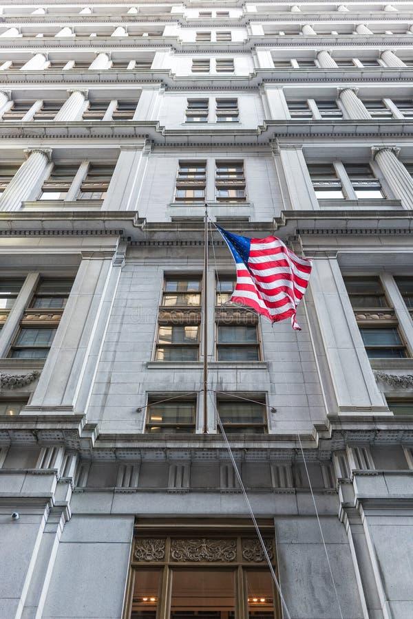 Amerikanische Flagge mit Gebäude hinten Weißer Hintergrund lizenzfreie stockfotografie
