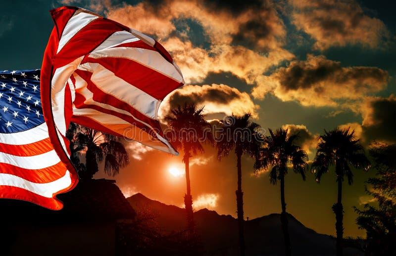 Amerikanische Flagge am Palmeschattenbild auf einem Hintergrund des tropischen Sonnenuntergangs lizenzfreie stockfotos