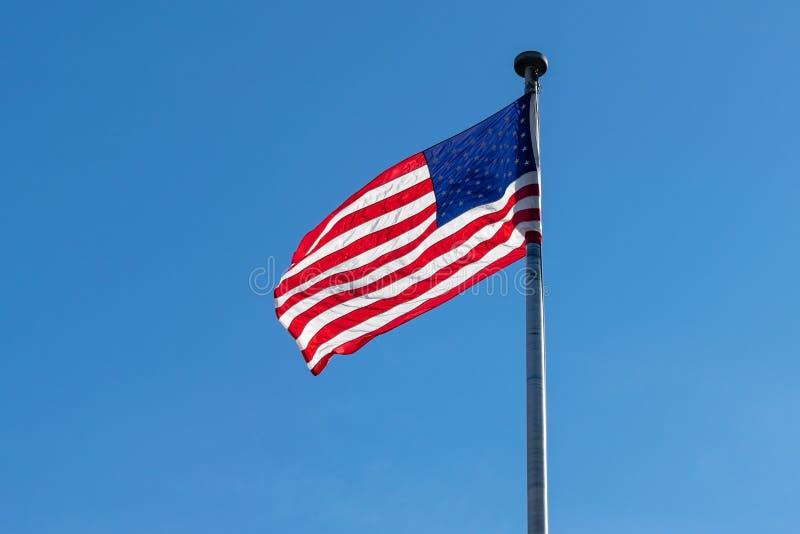 Amerikanische Flagge, Sterne u. Streifen, bewegend in den Wind, gegen einen schönen blauen Himmel an einem sonnigen Sommertag wel stockbild