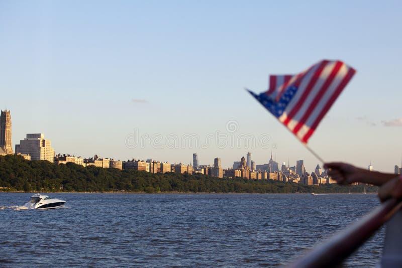 Amerikanische Flagge während des Unabhängigkeitstags auf Hudson River mit einer Ansicht bei Manhattan - New York City - Vereinigt lizenzfreie stockbilder