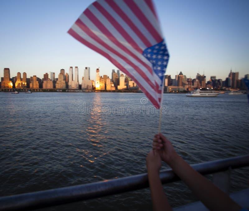 Amerikanische Flagge während des Unabhängigkeitstags auf Hudson River mit einer Ansicht bei Manhattan - New York City - Vereinigt stockbild
