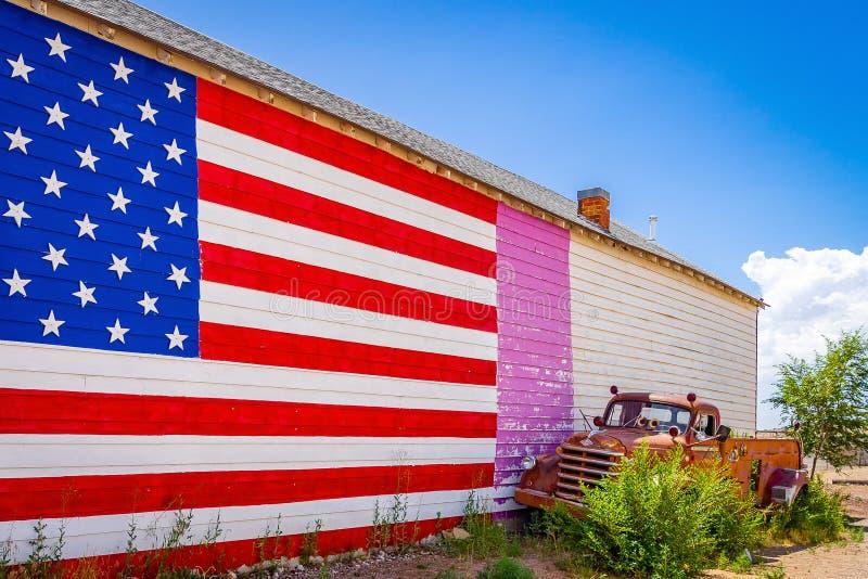 Amerikanische Flagge, Wand eines Hauses, altmodischer LKW auf Route 66, zieht Besucher von aller Welt Arizona an stockfotografie