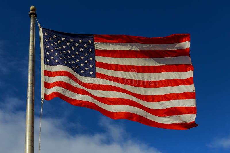 Amerikanische Flagge, welche die Brise gegen einen blauen Himmel mit weißen Wolken fliegt lizenzfreies stockbild