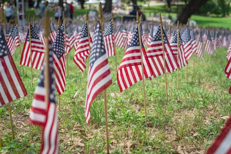 Amerikanische Flaggen auf Grasrasen und unscharfe Menschen im Hintergrund anlässlich der Gedächtnisfeier stockbilder