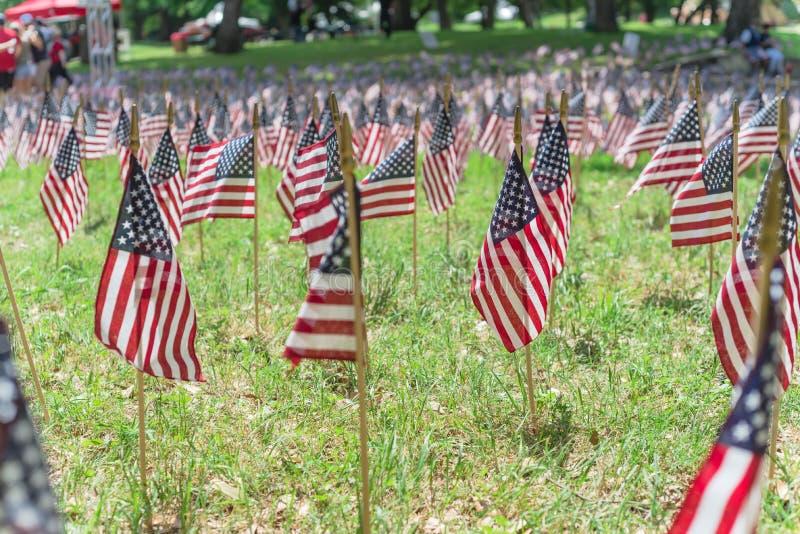Amerikanische Flaggen auf Grasrasen und unscharfe Menschen im Hintergrund anlässlich der Gedächtnisfeier stockfotos