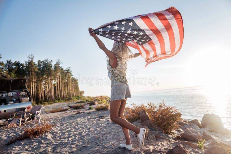 Amerikanische patriotische Frau, die in kompakten Anhänger mit ihrer Flagge reist lizenzfreies stockbild