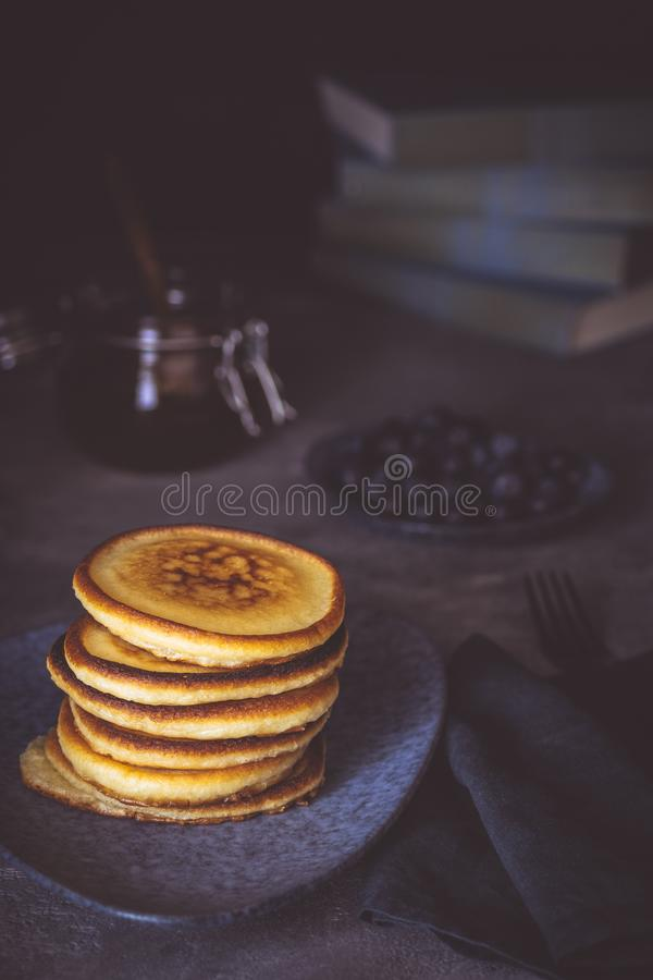 Amerikanische Pfannkuchen mit organischen Beeren und Ahornsirup auf dunklem Hintergrund Klassisches selbst gemachtes Frühstück lizenzfreies stockfoto
