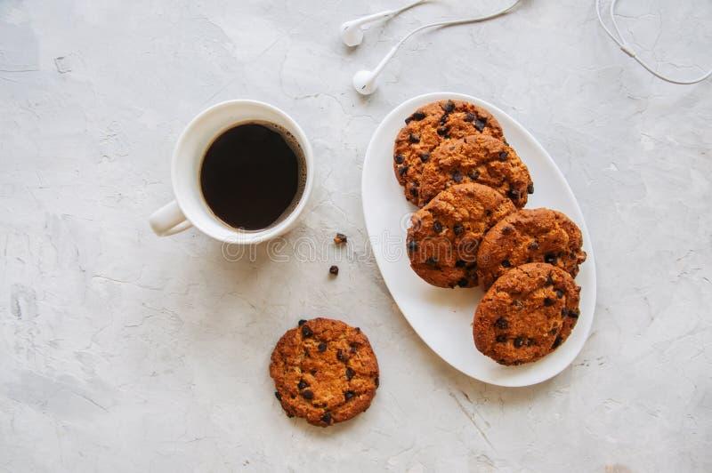 Amerikanische Schokoladensplitterplätzchen in einem weißen Plattentasse kaffee stockfotos