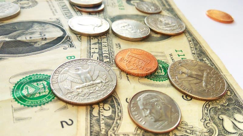 Amerikanische Viertel-, Groschen- und Pennymünzen auf Dollar-USA-Hintergrund stockbilder