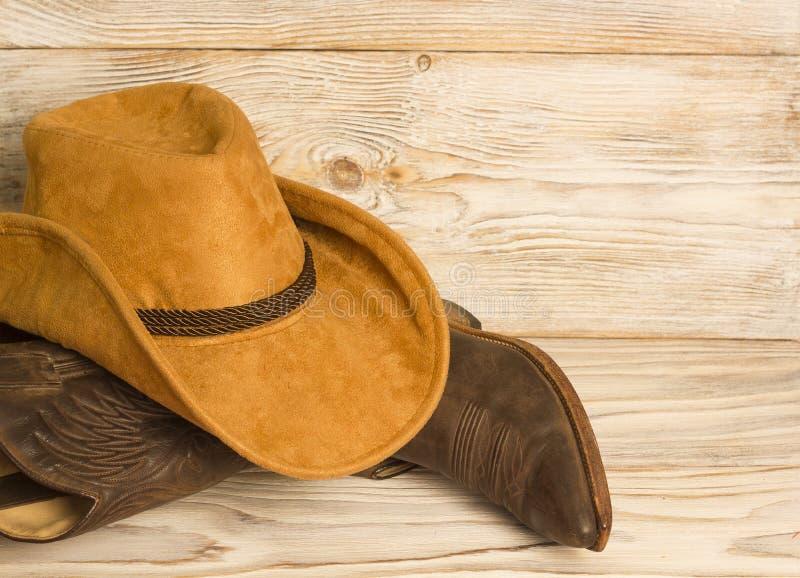 Amerikanische Westcowboystiefel und Hut auf hölzernem Beschaffenheitshintergrund stockfotos