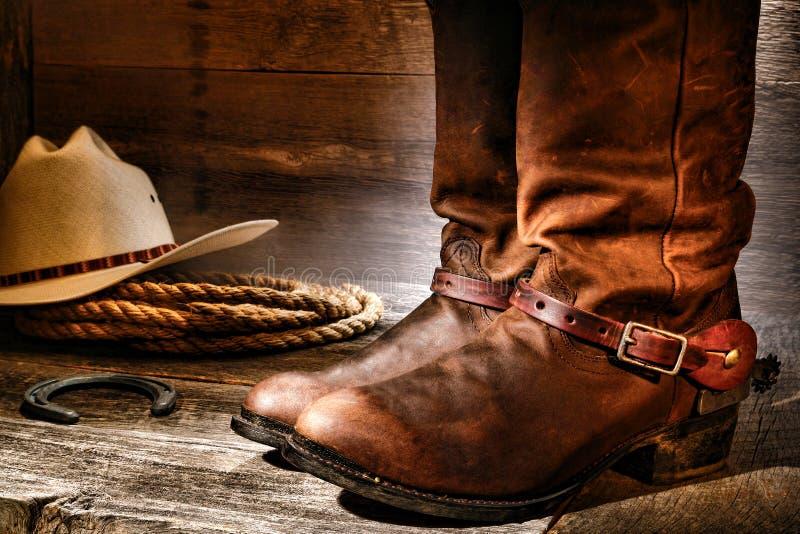 Amerikanische Westrodeo-Cowboystiefel im alten Ranch-Stall stockbilder