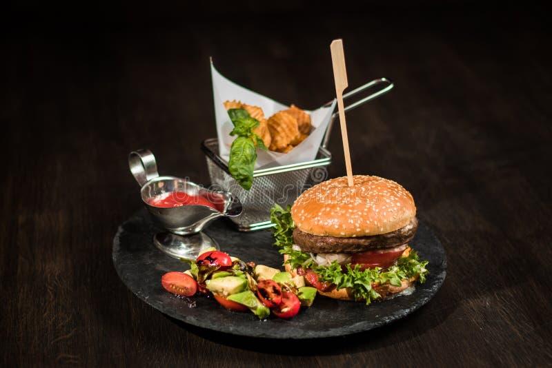 Amerikanischer Burger auf Schwarzblech, Chips, Salat, Soße lizenzfreies stockbild