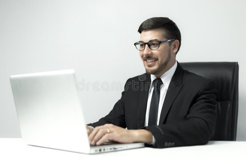 Amerikanischer junger Geschäftsmann, der mit Laptop im Büro arbeitet stockbilder