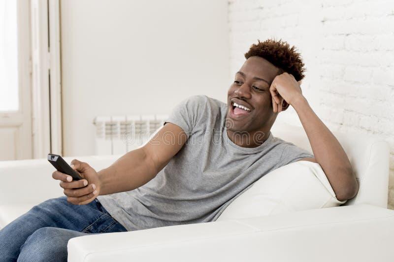 Amerikanischer Mann des attraktiven Schwarzafrikaners, der zu Hause aufpassendes Fernsehen der Sofacouch sitzt lizenzfreie stockfotos