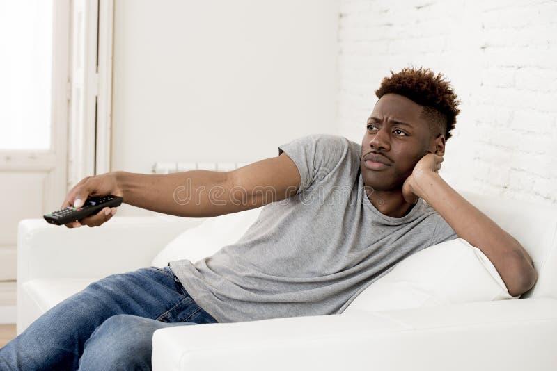 Amerikanischer Mann des attraktiven Schwarzafrikaners, der zu Hause aufpassendes Fernsehen der Sofacouch sitzt lizenzfreies stockbild