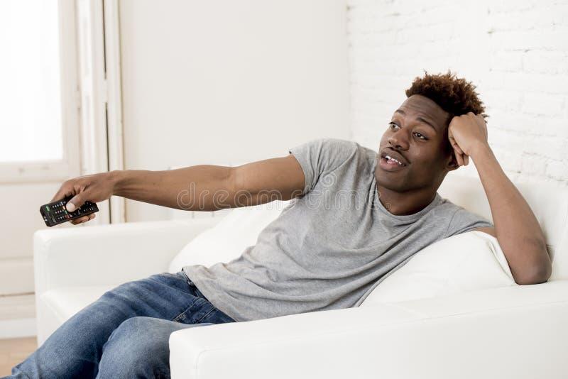 Amerikanischer Mann des attraktiven Schwarzafrikaners, der zu Hause aufpassendes Fernsehen der Sofacouch sitzt stockfoto