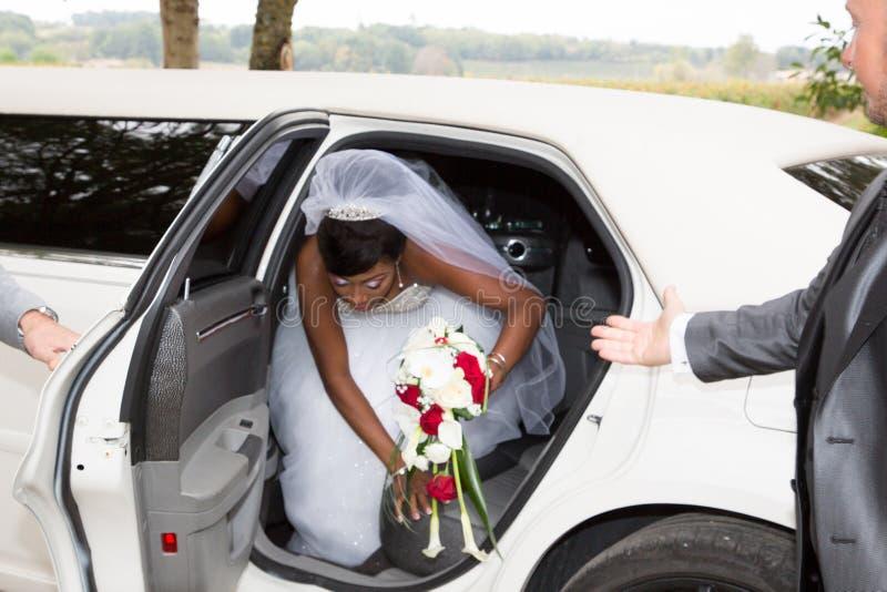 amerikanischer Schwarzafrikanerbraut-Schmuckkopf sitzt in einem weißen Auto am Hochzeitstag mit Blumen lizenzfreie stockfotografie