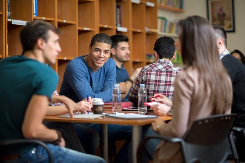 Amerikanischer Student des Latino, der mit Freunden gesellig ist stockbilder