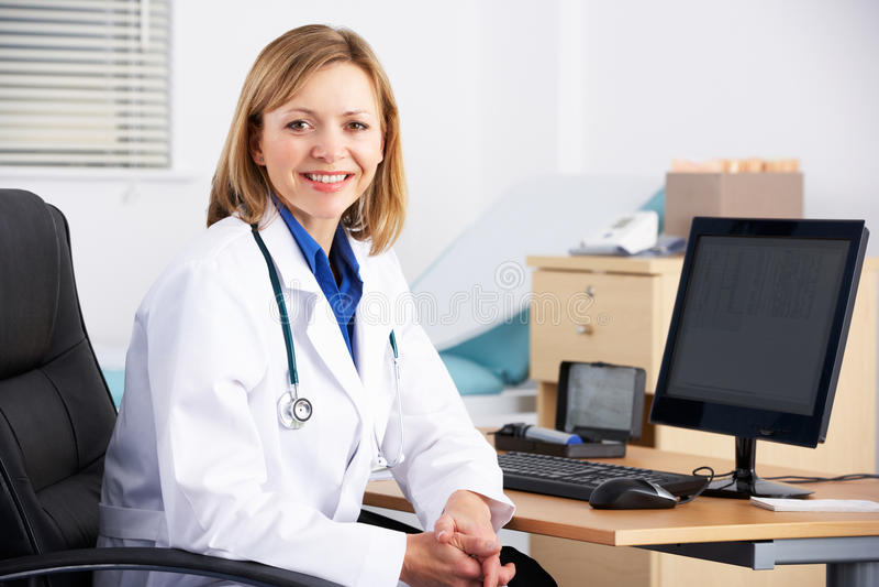 Amerikansk doktor för stående som sitter på skrivbordet royaltyfri fotografi