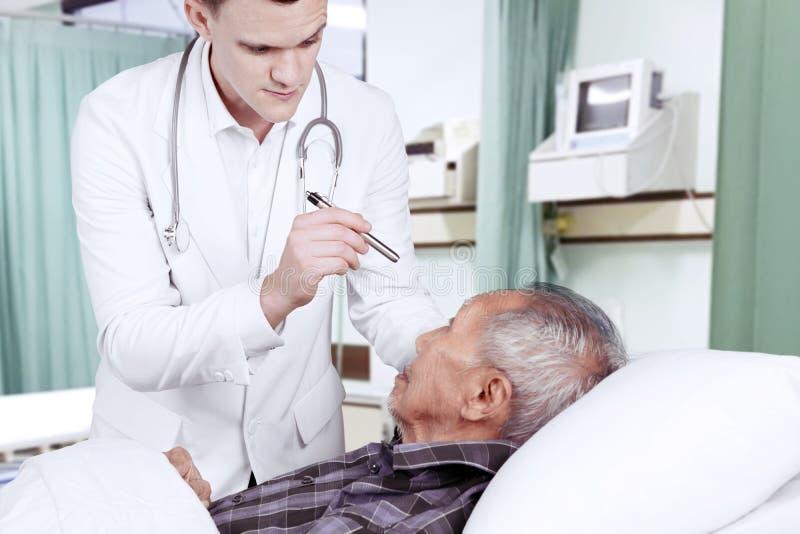 Amerikansk doktor som kontrollerar hans patientögon arkivfoto