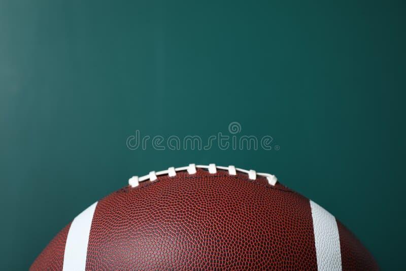 Amerikansk fotboll för nytt läder på den svart tavlan royaltyfri fotografi