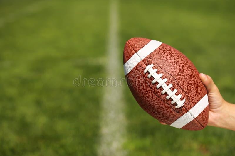 Amerikansk fotboll i hand över fält arkivfoto